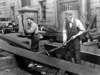 Shipworkers using a Ships Carpenters Adze