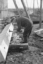 Shipwright Herbert Page from Hastings uses a foot adze to trim and shape a large timber.